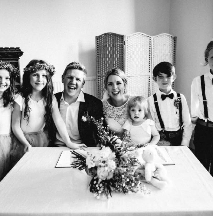 Photo of Charlotte and her husband and children on her wedding day