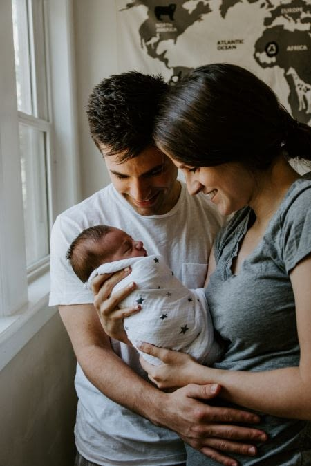 Newborn baby being held by smiling parents.